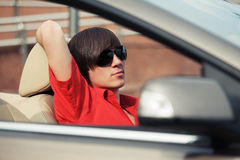 Young man in sunglasses driving convertible car. Young handsome man in sunglasses driving convertible car Royalty Free Stock Photo