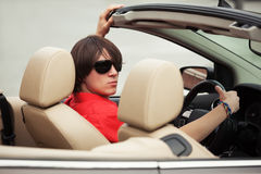 Young man in sunglasses driving convertible car. Young handsome man in sunglasses driving convertible car Stock Photo