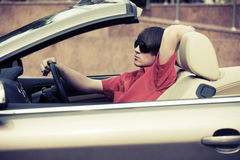 Young man in sunglasses driving convertible car. Young handsome man in sunglasses driving convertible car Royalty Free Stock Photography