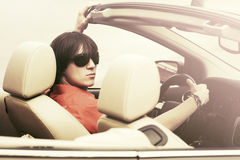 Young man in sunglasses driving convertible car. Young handsome man in sunglasses driving convertible car Royalty Free Stock Photos