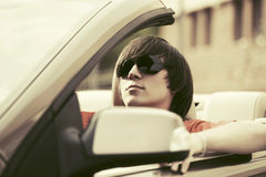 Young man in sunglasses driving convertible car. Young handsome man in sunglasses driving convertible car Stock Photography