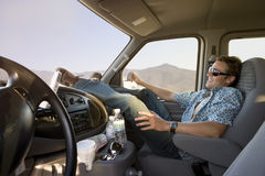 Young man in sunglasses with feet up in car, smiling, side view Royalty Free Stock Photo