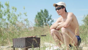 Young man in sunglasses fry the meat on the beach near the sea. Hot food Shashlik in Russia. Royalty Free Stock Images
