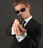 Young man with sunglasses and a gun Stock Image