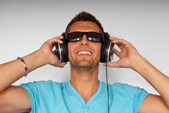 Young man in sunglasses with headphones Stock Image