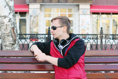 Young man in sunglasses and with headphones sits on bench Stock Image