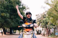 Young man in sunglasses and helmet riding motorcycle raising hands up as winner and success. Royalty Free Stock Image