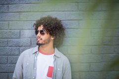 Young man in sunglasses. Leaning against wall Royalty Free Stock Photo