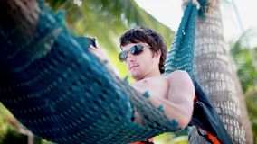 Young man in sunglasses lies on hammock using smartphone on beautiful exotic beach. 1920x1080 stock footage