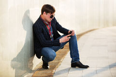 Young man in sunglasses looking at mobile phone Royalty Free Stock Photo