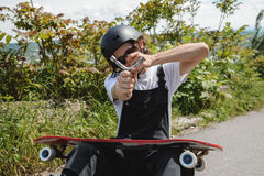 A young man in sunglasses and overalls with a helmet on his head changes his wheels on his longboard under the open sky royalty free stock photography