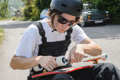 A young man in sunglasses and overalls with a helmet on his head changes his wheels on his longboard under the open sky stock images