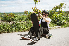 A young man in sunglasses and overalls with a helmet on his head changes his wheels on his longboard under the open sky royalty free stock image