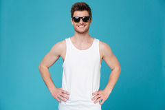 Young man in sunglasses posing isolated. Photo of young man in sunglasses posing isolated over blue background. Looking at camera Royalty Free Stock Images