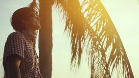 Young man in sunglasses rests sitting on a palm tree, above the water against the backdrop of the sea and sunset, slow. Young man rests sitting on a palm tree stock video footage