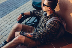 Young Man In Sunglasses Rests On Steps Next To Bicycle Holiday Activity Resting Concept. A young man cyclist with a backpack in sunglasses sits and rests on the Royalty Free Stock Images
