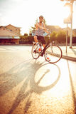 Young man in sunglasses riding a bicycle on a city street at sun Stock Images