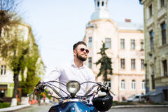Young man in sunglasses riding scooter along the street city Stock Image