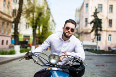 Young man in sunglasses riding scooter along the street city Stock Photography