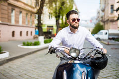 Young man in sunglasses riding scooter along the street city Royalty Free Stock Image