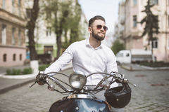 Young man in sunglasses riding scooter along the street city toned Royalty Free Stock Photos
