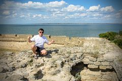 Young man in sunglasses sits on the wall of the fortress by the sea. The walls of the ackerman fortress in Odessa 2018 Royalty Free Stock Photo