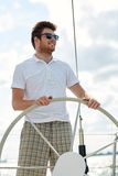 Young man in sunglasses steering wheel on yacht Stock Image