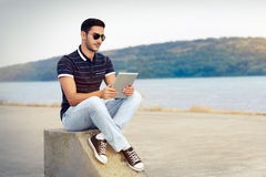 Young Man with Sunglasses and Tablet by the Water Stock Image