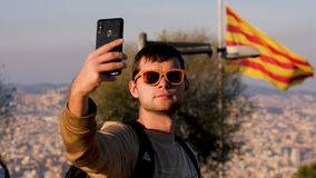 Young man in sunglasses taking selfie against the background of the flag of barcelona. Tourist with telephone in hand. Young man in sunglasses taking selfie stock footage