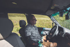 Young Man Driver With Tattoo Rests During Road Adventure. Trip Travel Journey Lifestyle Concept. A young man in sunglasses with a tattoo on his arm, sits in the Royalty Free Stock Photos
