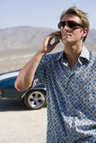 Young man in sunglasses using mobile phone by car in desert Royalty Free Stock Photography
