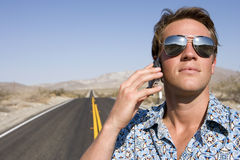 Young man in sunglasses using mobile phone on open road, close-up. Young men in sunglasses using mobile phone on open road, close-up Royalty Free Stock Photos