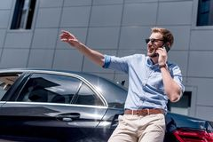 Young man in sunglasses using smartphone while standing. At car Stock Photo