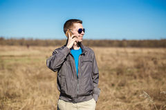 Young man with sunglasses and windbreaker talking on the mobile phone. There is a  field as background Stock Photography