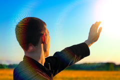 Young Man On Sunset. Young Man stretch his Hand to the Sunlight in the Evening Fields Royalty Free Stock Photography