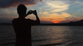 The young man, sunset, mountain lake, phone stock video footage