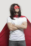 Young man in super hero costume standing with arms crossed against gray background Royalty Free Stock Image