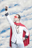 Young man in superhero costume with hand raised against cloudy sky Stock Photos