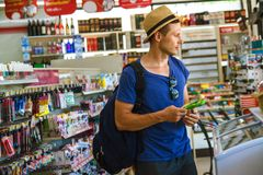Young man in supermarket choosing products . royalty free stock images