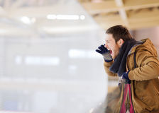 Young man supporting hockey game on skating rink Stock Photo
