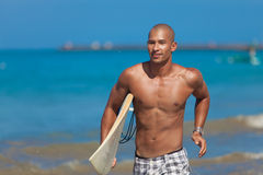 Young man with surfboard. Young muscular man running with surfboard on beach in Bali Stock Image