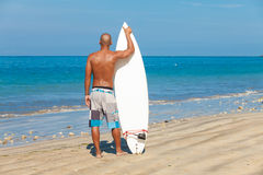 Young man with surfboard. Young man holding surfboard on beach in Bali Stock Images