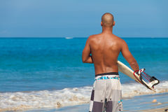Young man with surfboard. On beach in Bali Stock Photo