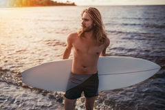 Young man with surfboard. Young handsome man with long hair is standing on beach with white surfboard in hands royalty free stock image
