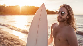 Young man with surfboard. Young handsome man with long hair is standing on beach with white surfboard in hands royalty free stock photography