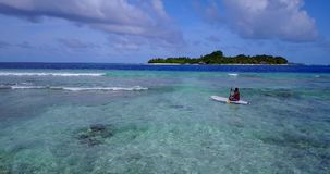 V08023 young man on a surfboard paddleboard with aerial flying drone view in blue clear sea water ocean Royalty Free Stock Photography