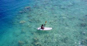 V08040 young man on a surfboard paddleboard with aerial flying drone view in blue clear sea water ocean Royalty Free Stock Photo