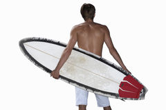 Young man with surfboard, rear view, mid-section, cut out Stock Images