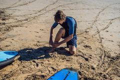 Young man surfer getting on the surfboard`s leash.  Stock Photos