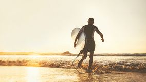 Young man Surfer taking surfboard and running with long surf board to waves on the evening sunset sky background. Active holidays royalty free stock photo